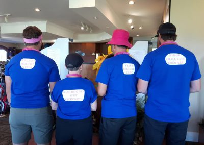 Fore for Shan 2019: Golfers show off the back of their golf shirts with Breast Cancer messaging